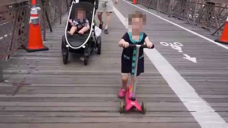 This is a Screenshot from a YouTube Video - A 2-Year-Old Rides her Scooter Along Brooklyn Bridge Without a Helmet (towards oncoming crowds) !!